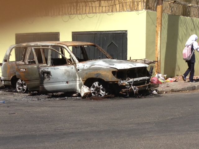 A burned-out vehicle outside the embassy belonging to embassy staff.