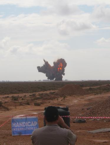 A cameraman films the explosion of 25 tonnes of ammunition (Photo: Handicap International)