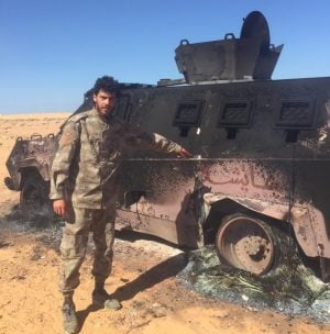 LNA soldier beside a wrecked BDB personnel carrier (Photo: social media)